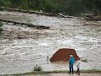 PHOTO: Local residents look over a road washed out by a torrent of water following overnight flash flooding near Left Hand Canyon, south of Lyons, Colo., on Sept 12, 2013.