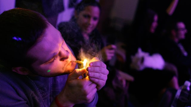 PHOTO: A man smokes marijuana on the official opening night of Club 64, a marijuana-specific social club, where a New Year's Eve party was held, in Denver, Dec. 31, 2012.