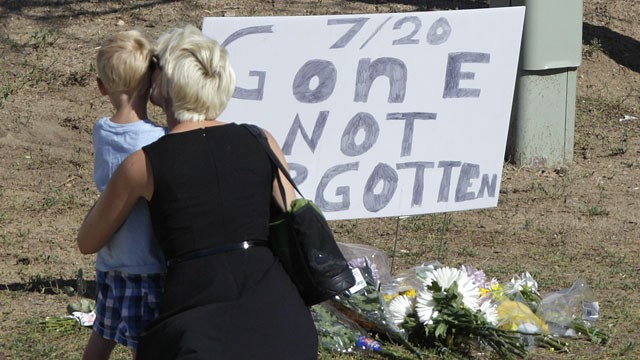 "PHOTO: A woman and a child stand near a sign that reads ""7/20 Gone Not Forgotten,"" near the movie theater where a gunman killed at least 12 people and wounded dozens of others in one of the deadliest mass shootings in recent U.S. history, Friday, July 20,"