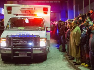 PHOTO: Mourners stand at attention as the bodies of two fallen NYPD police officers are transported from Woodhull Medical Center, Saturday, Dec. 20, 2014, in New York.