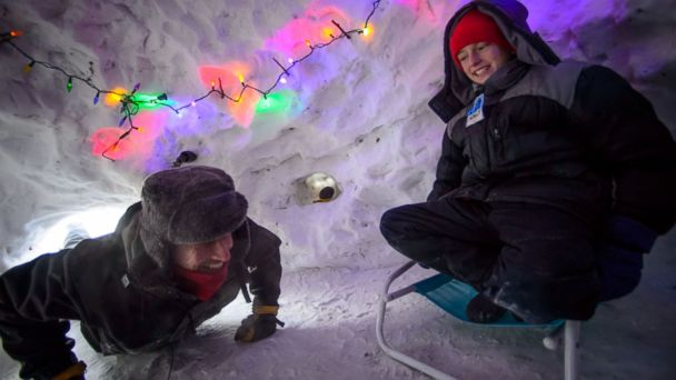 PHOTO: Eli Esch, right, and his father Tom enjoy the snow fort and igloo they built over the last few weeks, on Jan. 6, 2014 in Minn
