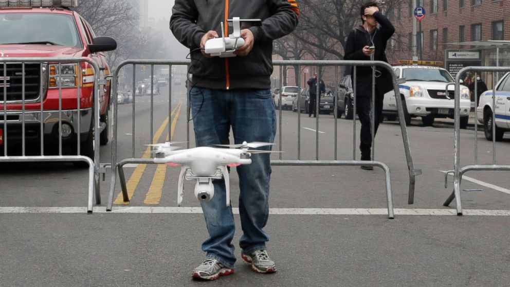 PHOTO: Brian Wilson launches a small drone equipped with a video camera to fly over the scene of an explosion an explosion that leveled two apartment buildings in East Harlem, March 12, 2014, in New York.