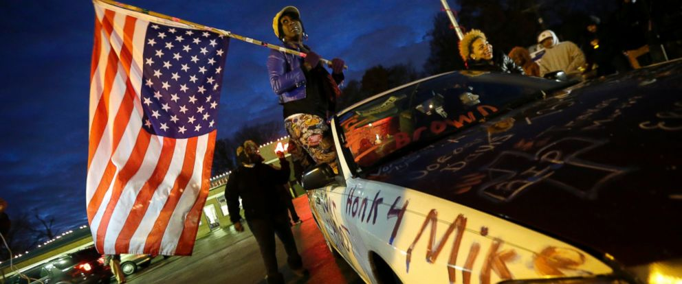 PHOTO: Gina Gowdy holds an upside-down American flag, Nov. 24, 2014, in Ferguson, Mo., more than three months after an unarmed 18-year-old man was shot and killed there by a policeman.