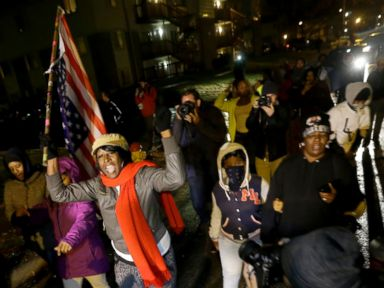 PHOTO: Protesters march Saturday, Nov. 22, 2014, along a stretch of road where violent protests occurred following the August shooting of unarmed black teenager by a white police officer in Ferguson, Mo.
