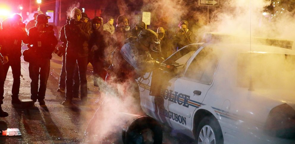 PHOTO: A police officer approach a police vehicle after a protester has thrown a smoke device from the crowd Tuesday, Nov. 25, 2014, in Ferguson, Mo.