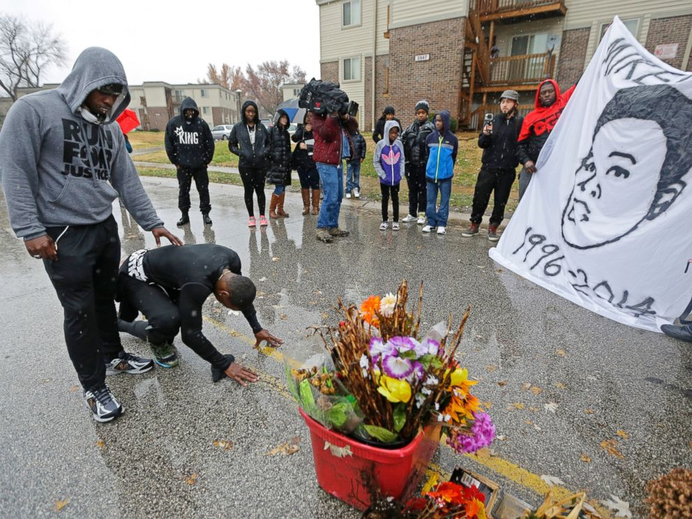 PHOTO: Ray Mills, left, and Londrelle Hall pause before a memorial in the middle of a street Sunday, Nov. 23, 2014, more than three months after a black 18-year-old was shot and killed there by a white policeman in Ferguson, Mo.