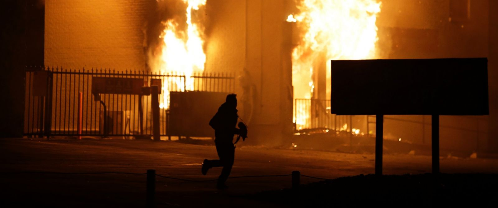 PHOTO: A man runs away from the burning storage facility after the announcement of the grand jury decision not to indict officer Darren Wilson, Nov. 24, 2014, in Ferguson, Mo.
