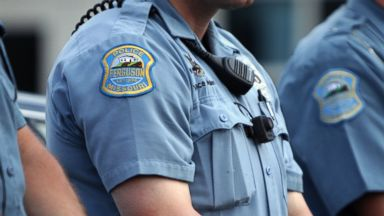PHOTO: Police officers wear what appear to be body cameras as they hold the line against protesters gathered at the police station during a rally in Ferguson, Mo. on Aug. 30, 2014.