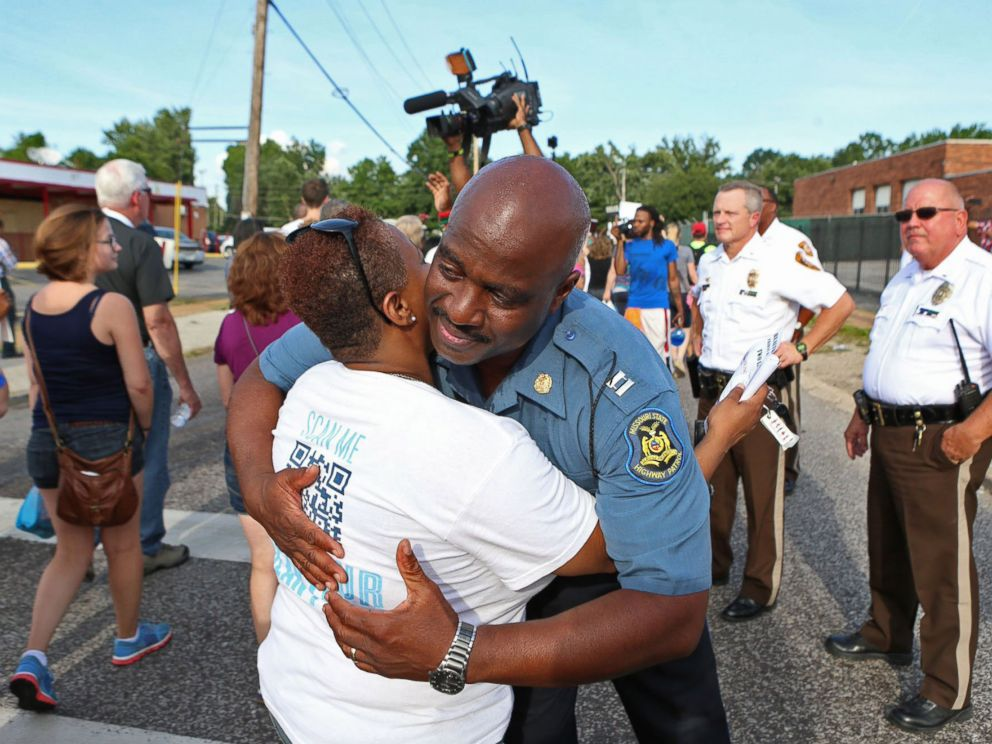 PHOTO: Capt. Ronald Johnson of the Missouri Highway Patrol hugs Angela Whitman, of Berkeley, Mo., on West Florissant Avenue in Ferguson, Mo., on Aug. 14, 2014.