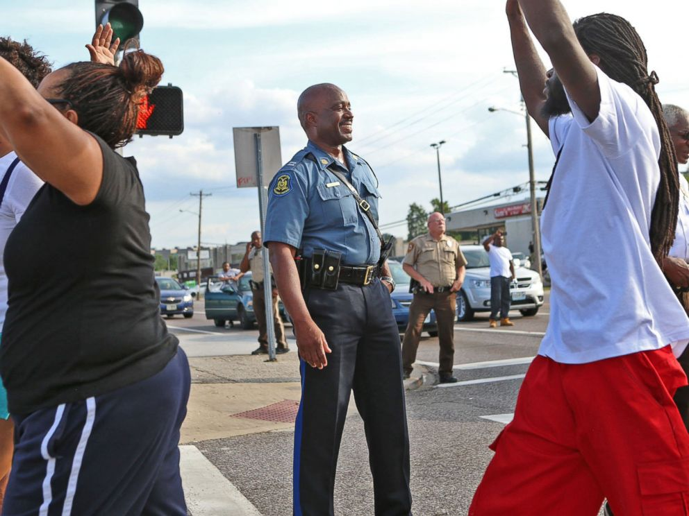 PHOTO: Capt. Ronald Johnson of the Missouri Highway Patrol smiles at demonstrators march along West Florissant Avenue in Ferguson, Mo., on Aug. 14, 2014.