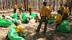 PHOTO: Phillip Maldonado, a squad leader with the Granite Mountain Hotshots, trains crew members on setting up emergency fire shelters in 2012.