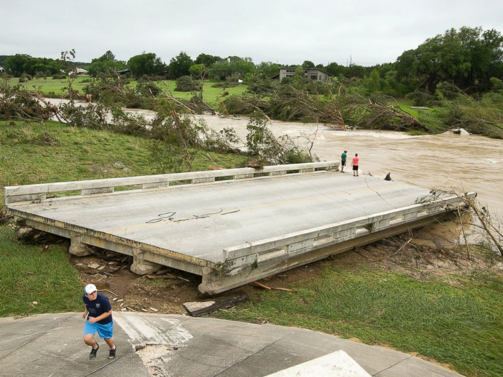 PHOTO: Dustin McClintock, of Wimberley,, Brandon Bankston, of Blanco, Hesston Krause, of Smithson Valley, look at the Fischer Store Road bridge over the Blanco River near Wimberley, Texas, which was destroyed in a flood on Sunday May 24, 2015.