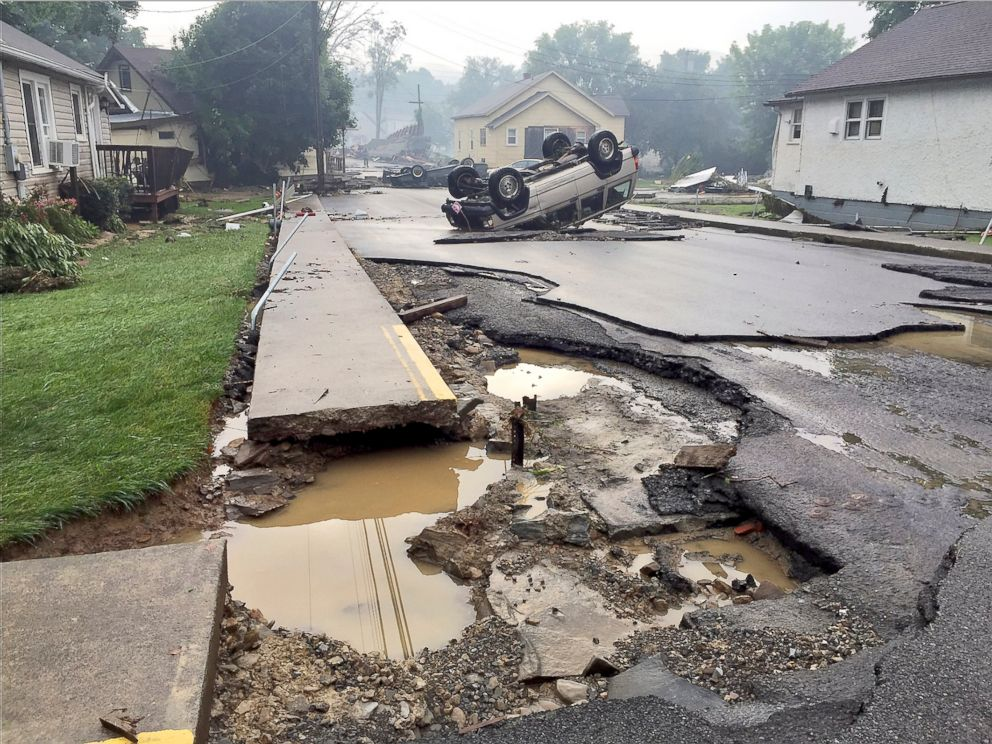 Overturned vehicles sit on a heavily damaged road after flooding near ...