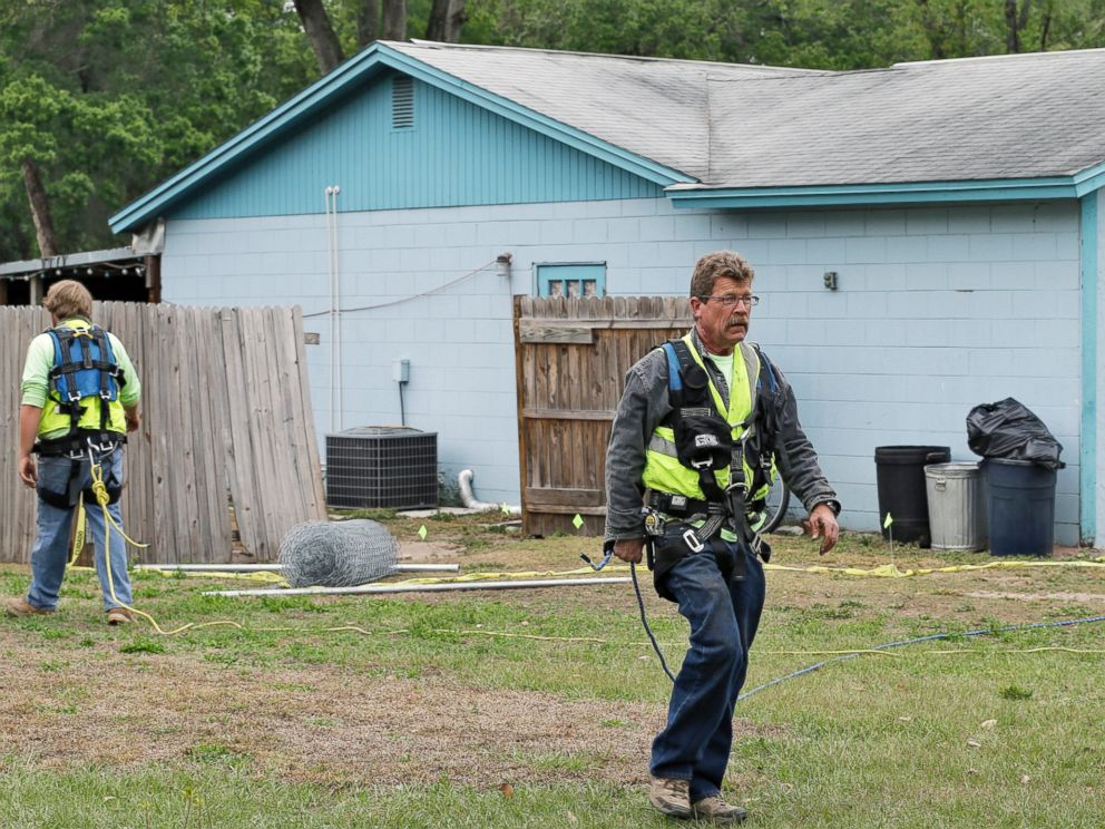 PHOTO: Engineers in safety equipment cross in front of a home where a sinkhole opened up underneath a bedroom and swallowed Jeffrey Bush, in Seffner, Fla., March 2, 2013.