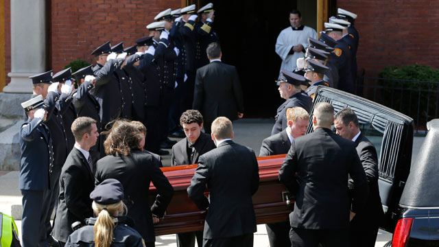 PHOTO: An honor guard from area Fire Departments salute as pallbearers carry the casket of Boston Marathon bomb victim Krystle Campbell into St. Josephs Church for her funeral
