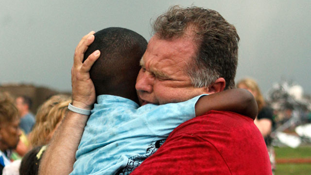 PHOTO: A teacher hugs a child at Briarwood Elementary school after a tornado destroyed the school in south Oklahoma City, May 20, 2013.