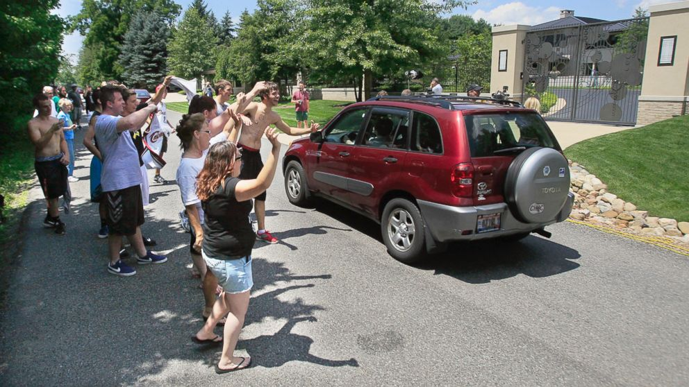 PHOTO: In this July 11, 2014 file photo, Cleveland Cavaliers basketball fans celebrate in front of the house of LeBron James, in Bath, Ohio, after learning of James decision to sign as a free-agent with the Cavaliers.