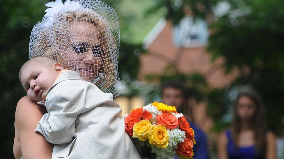 PHOTO: Christine Swidorsky carries her son and the couples best man, Logan Stevenson, 2, down the aisle to her husband-to-be Sean Stevenson during the wedding ceremony on Aug. 3, 2013 in Jeannette, Pa.