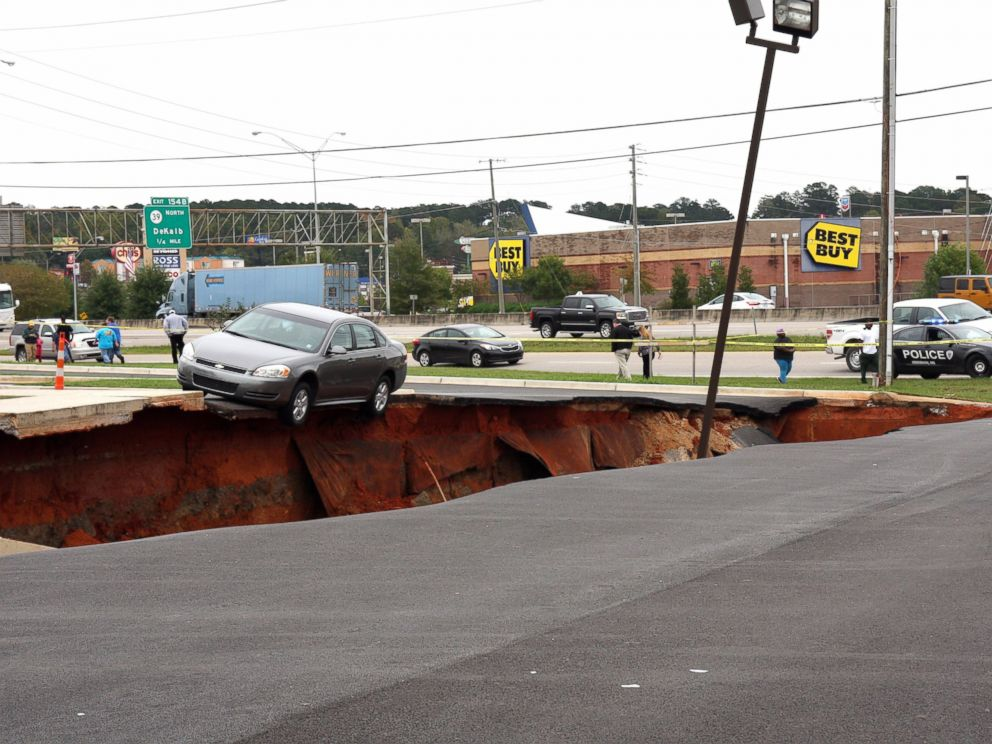 PHOTO: A car teeters on the edge of a cave-in of a parking lot in Meridian, Miss., Sunday, Nov. 8, 2015.