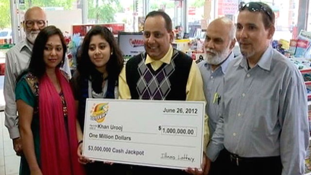 PHOTO: Urooj Khan, center, holds a ceremonial check in Chicago for $1 million as winner of an Illinois instant lottery game, June 2012. At left, is Khans wife, Shabana Ansari.