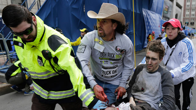 PHOTO: Medical responders run an injured man past the finish line the 2013 Boston Marathon following an explosion in Boston, April 15, 2013.