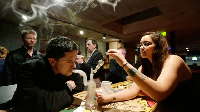 PHOTO: A patron inhales marijuana vapor just after midnight March 2, 2013, with the help of a bar worker in the upstairs lounge area of Stonegate, a pizza-and-rum bar in Tacoma, Wash.