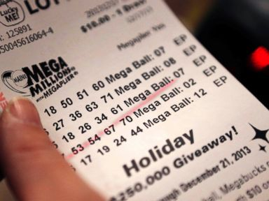 PHOTO: A cashier holds a Mega Millions lottery ticket at a convenience store in Lisbon, Maine, Tuesday, Dec. 17, 2013.