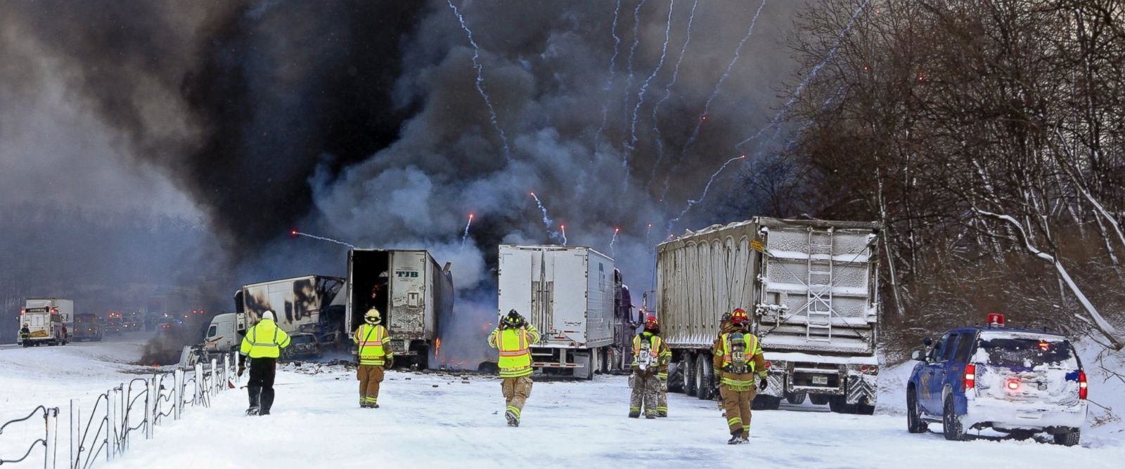 PHOTO: Emergency personnel watch as fireworks ignite at the scene of a fiery crash that closed both sides of Interstate 90, on Jan. 9, 2015, between mile markers 88 and 92 in eastern Kalamazoo County, near Galesburg, Mich.