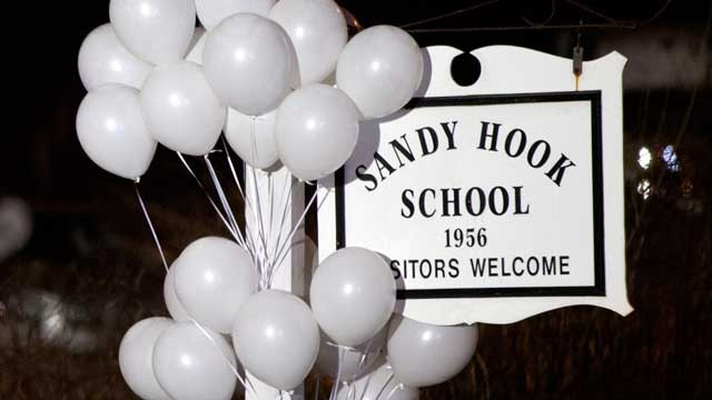 PHOTO: White balloons decorate the sign for the Sandy Hook Elementary School as a Connecticut State Trooper stands guard at the school's entrance, Dec. 15, 2012, in Newtown, Conn.