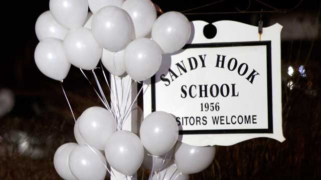 PHOTO: White balloons decorate the sign for the Sandy Hook Elementary School as a Connecticut State Trooper stands guard at the schools entrance, Dec. 15, 2012, in Newtown, Conn.