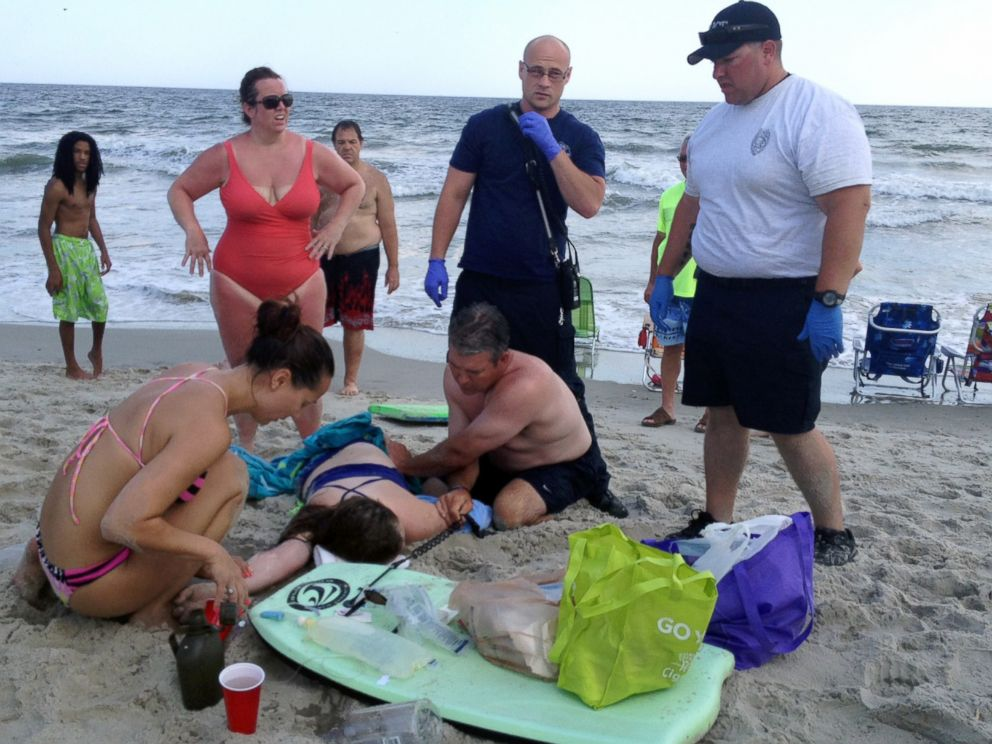 PHOTO People Assist A Teenage Girl At The Scene Of Shark Attack In Oak