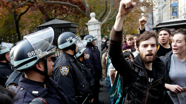 PHOTO: Police in riot gear watch as Occupy Wall Street protesters march past City Hall in New York, Nov. 15, 2011.