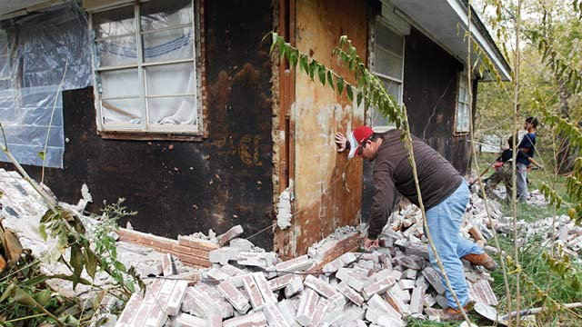 PHOTO: Man clears bricks from house after earthquake