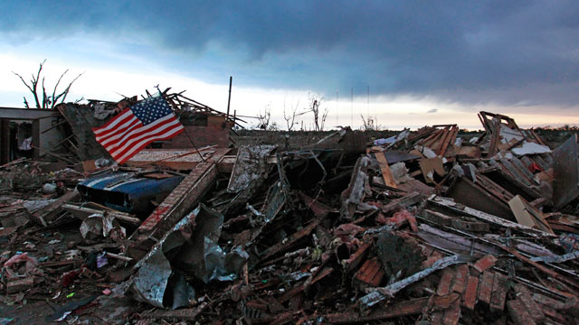 PHOTO: An American flag blows in the wind at sunrise atop the rubble of a destroyed home in Moore, Okla., on May 21, 2013, a day after a tornado roared through the Oklahoma City suburb, flattening entire neighborho