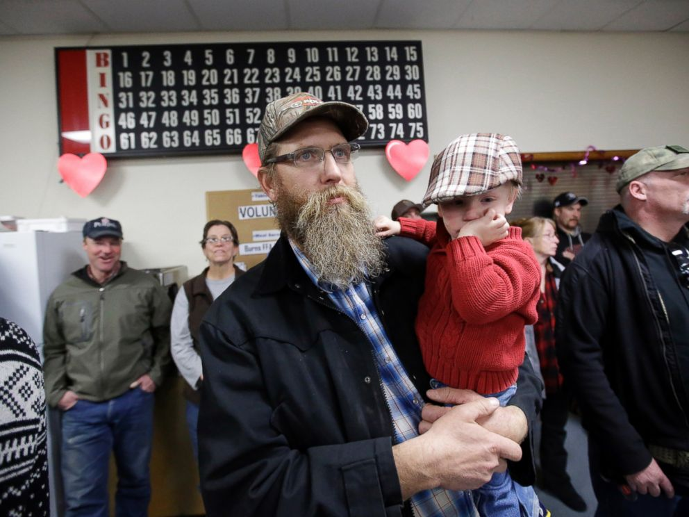 PHOTO: Tom Schaefer holds his son Isaac, while looking on during the Harney County committee of safety town hall called to discuss the occupation of the Malheur National Wildlife Refuge Friday, Jan. 8, 2016, in Burns, Ore.