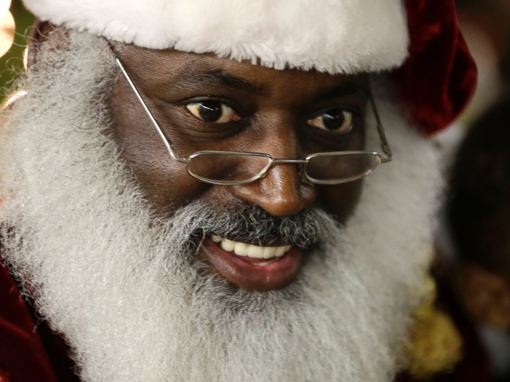 PHOTO: In this Dec. 17, 2013 photo, Dee Sinclair, portraying Santa Claus, reads a story to children in Atlanta. Kids dont see color. They see a fat guy in a red suit giving toys, says Sinclair.