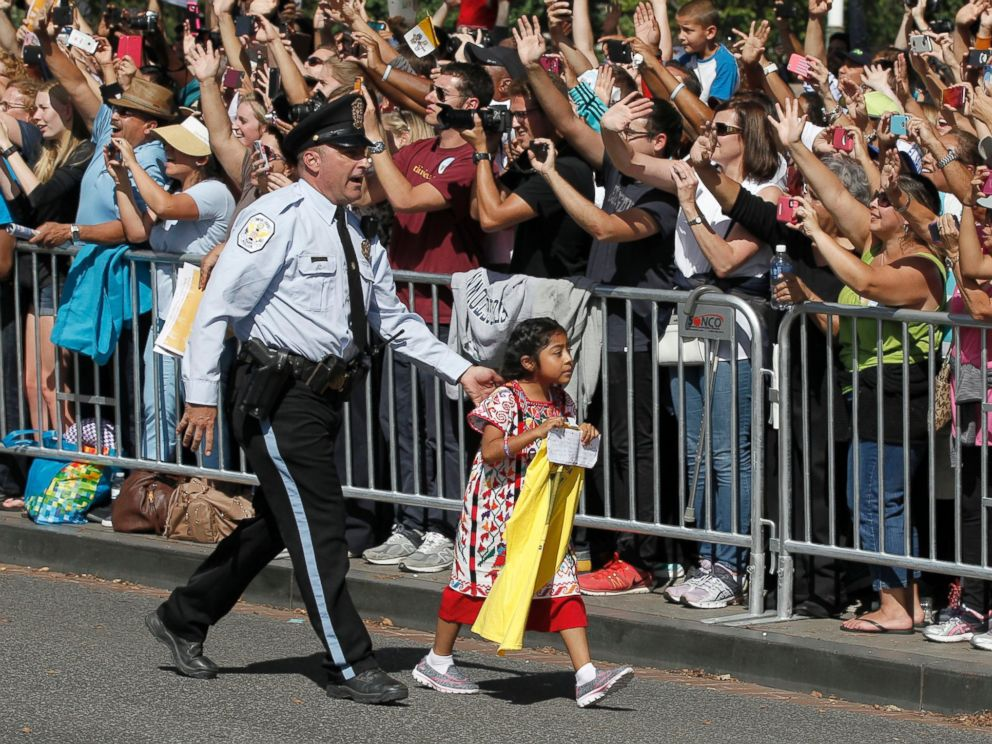PHOTO: A child is escorted by police during a parade for Pope Francis in Washington, Sept. 23, 2015.