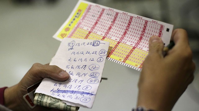PHOTO:&nbsp;Sharon Long double checks her Powerball numbers as she stands in line in a convenience store in Baltimore, Wednesday, Nov. 28, 2012. Long, a customer service representative for a plumbing company, picked numbers that her sister asked her to play wi
