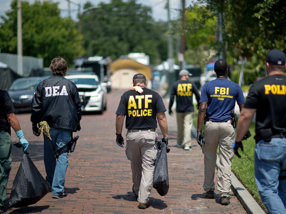 PHOTO: Federal and local law enforcement officials walk through the street next to the scene of a mass shooting at a nightclub, June 13, 2016, in Orlando, Fla.