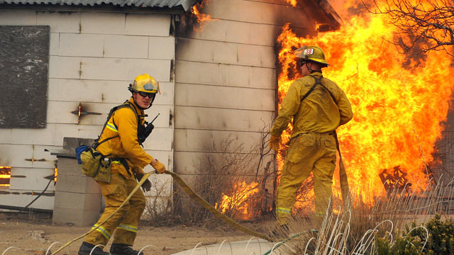 PHOTO: Firefighters wait for water before attacking an outbuilding adjacent to a home, Jan. 19, 2012 in Pleasant Valley, Nev.