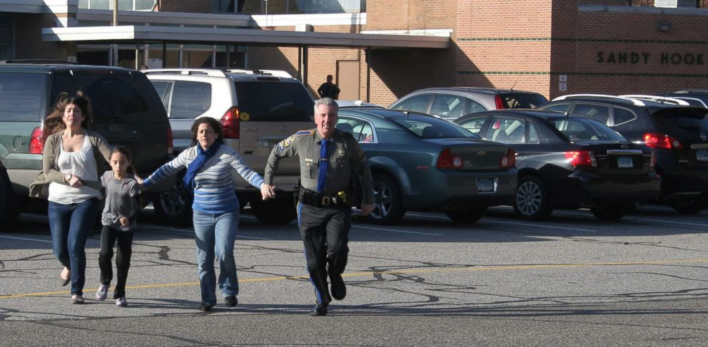 PHOTO: A police officer leads two women and a child from Sandy Hook Elementary School in Newtown, Conn., in this Dec. 14, 2012 photo.