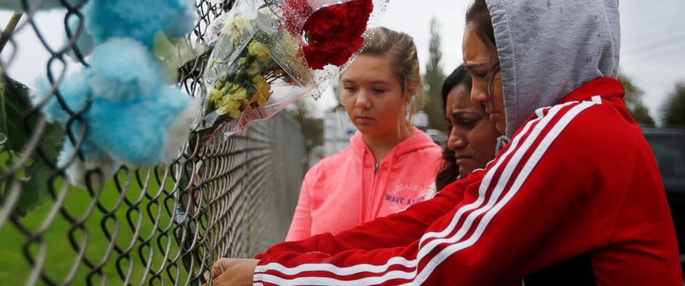 PHOTO: Student Tyanna Davis, right, places flowers on the fence bordering Marysville-Pilchuck High School in Marysville, Wash., Oct. 25, 2014.