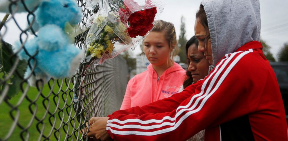 PHOTO: Marysville Pilchuck student Tyanna Davis, right, places flowers on the fence bordering Marysville Pilchuck High School in Marysville, Wash., Saturday, Oct. 25, 2014.