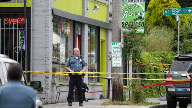 PHOTO: A Seattle Police officer stands outside a cafe where a gunman opened fire, killing two people and critically wounding three others on May 30, 2012.
