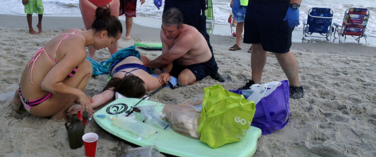 PHOTO: People assist a teenage girl at the scene of a shark attack in Oak Island, N.C., Sunday, June 14, 2015.