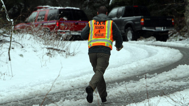 PHOTO: A man with King County Search and Rescue runs toward scene of avalanche at exit 47 along I-90 near Snoqualmie Pass, Sat. April 13, 2013.