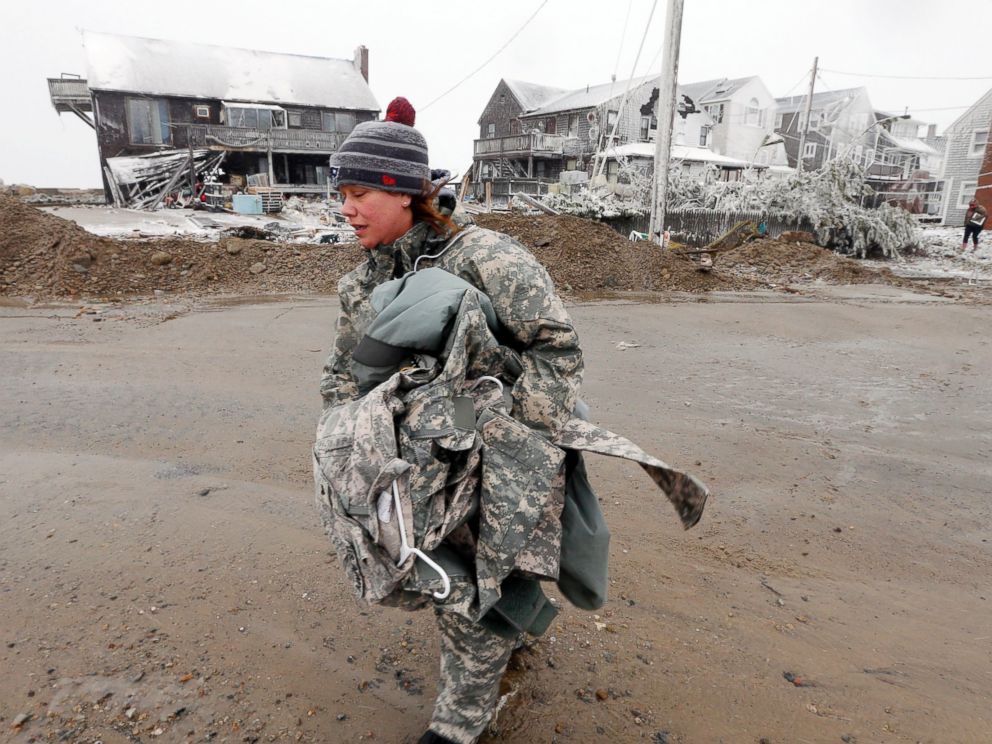 PHOTO: U.S. Army soldier Jennifer Bruno carries some belongings from her house, center rear, that was heavily damaged by storm surge during a winter storm, Jan. 27, 2015, in Marshfield, Mass.