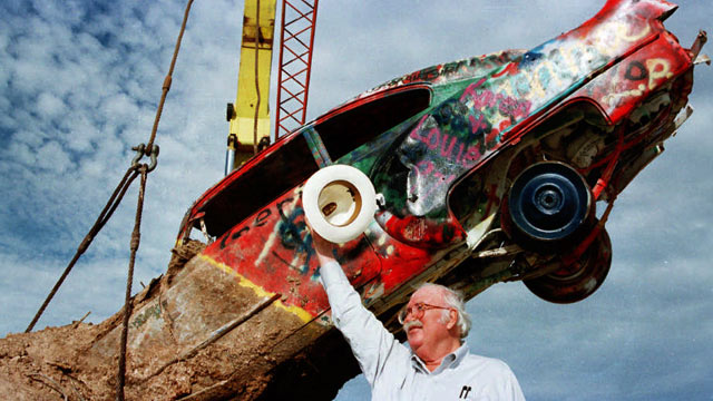PHOTO: Stanley Marsh 3, dubbed Amarillos eccentric millionaire, watches as workers lower into place one of the ten cadillacs that made up the Cadillac Ranch west of Amarillo, Texas.