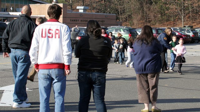 PHOTO: In this photo provided by the Newtown Bee, people look on as students are led out of Sandy Hook Elementary School in Newtown, Conn., where authorities say a gunman opened fire, killing 26 people, including 20 children on Dec. 14, 2012.