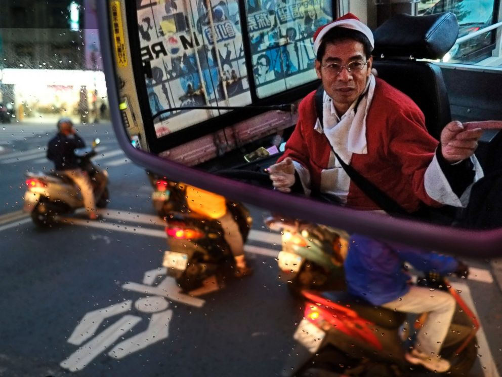 PHOTO: Reflected in a mirror, a public bus driver dressed as Santa Claus gives a passenger directions on Dec. 18, 2013, in Taipei, Taiwan.